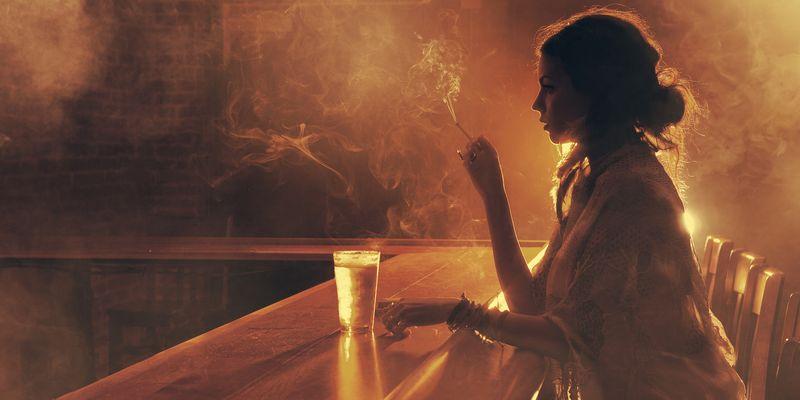 Девушка курит в баре